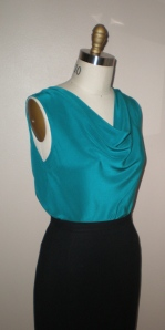 Top turned backwards, worn with cowl drape in front.